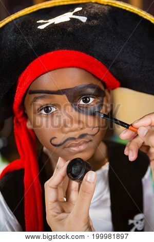 Hand of woman drawing on boy eyes at home