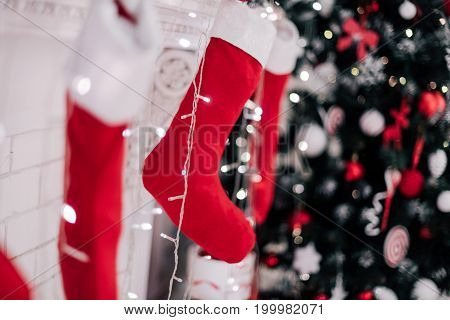 A Close Picture Of Beautifully Decorated Bright Red Christmas Socks Hanging On A Fireplace Waiting F