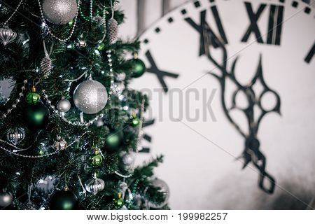 Green Christmas Tree In The Background Is A Large Decorative Clock Showing Midnight.