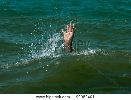 A girl drowning in the sea. Hand over water asking for help.