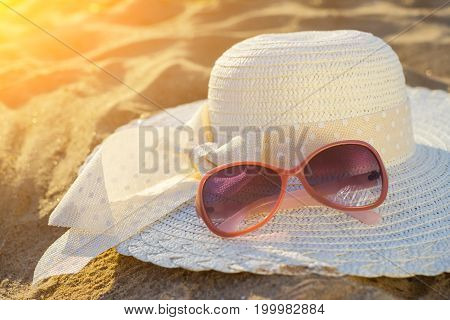 beach background with hat and glasses of red