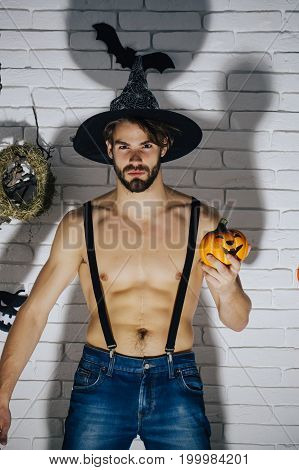 Halloween man in witch hat with pumpkin. Macho with muscular torso and dark shadow. Holiday traditional symbols on white brick wall. Jack o lantern. Mystery and horror concept.