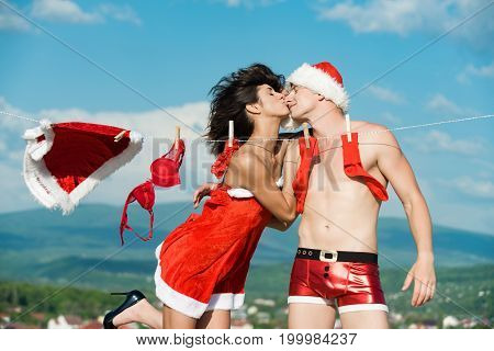 Xmas red costume on rope with pin. Couple of happy man and girl hanging clothes for drying. Christmas man and woman family. Laundry and dry cleaning. New year guy with muscular body on blue sky.