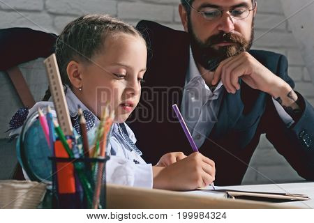 Kid and man sit by desk with school supplies. Schoolgirl and her dad with serious faces do homework. Girl and father in classroom on white brick background. Back to school and home schooling concept