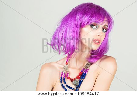 Woman in violet wig with fashionable makeup. Hairdresser salon and barbershop. Fashion model with red lips. Beauty and fashion. Girl with bright artificial hair in ethnic jewelry.