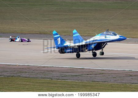 Zhukovsky, Moscow Region, Russia - August 28, 2015: Mikoyan Gurevich MiG-29UB 1 WHITE of russian air force perfoming race with Formula 3 car in Zhukovsky during MAKS-2015 airshow.