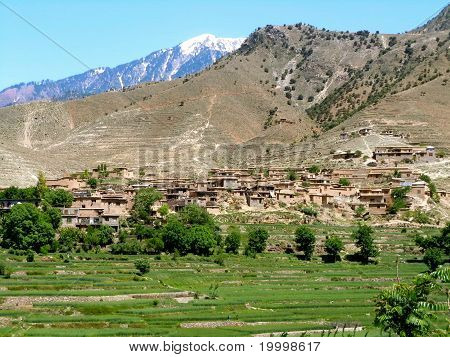 local village close to Hindu Kush in Kunar province Afghanistan. White snow cap mountain is already in Pakistan. poster