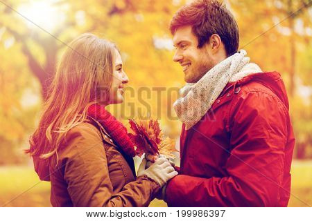 love, relationships, season and people concept - happy young couple with maple leaves in autumn park