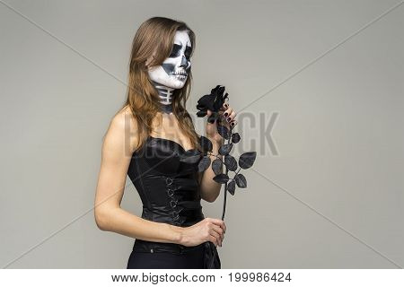 Portrait of young beautiful girl with fearful halloween skeleton makeup holding black rose flower over gray background.