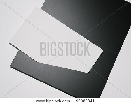 Black envelope with white blank sheet on dark floor. 3d rendering