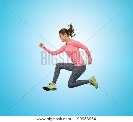 sport, fitness, motion and people concept - happy smiling young woman jumping in air over blue background