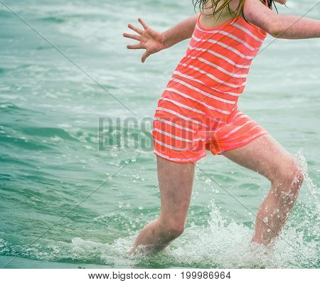 Retro Style Detail Of A Child In Old Fashioned Swimsuit Playing In The Ocean Waves