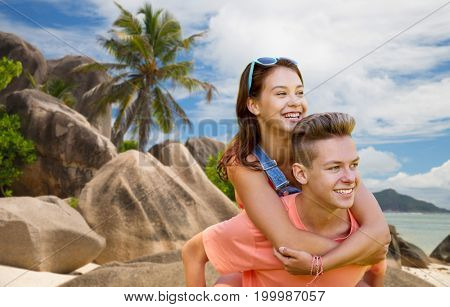 summer holidays, love and people concept - happy smiling teenage couple having fun over exotic seychelles beach background