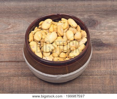 Organic dry broad haba beans in ceramic bowl on wooden vintage background