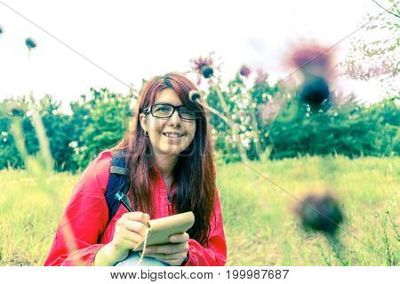 Picture of thistle and brunette with notepad and pencil in woods during day