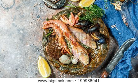 Seafood on brown ceramic plate on table with knives, blue cloth, lemon, greens