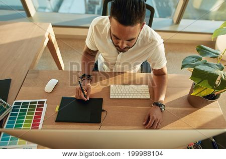 Top view shot of young man working in office using graphics tablet and computer. Male creative profession at his work desk.