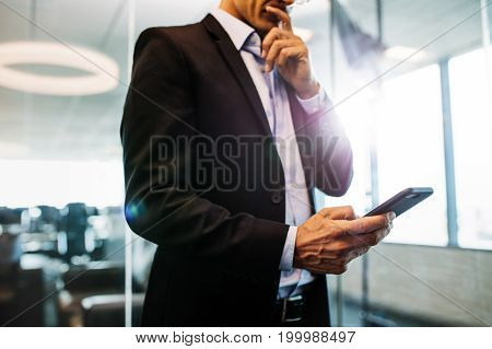 Cropped shot of businessman using mobile phone in office. Close up of male hands holding smart phone.