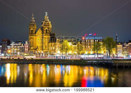Amsterdam, Netherlands - April 20, 2017: Beautiful night in Amsterdam. Night illumination of buildings and boats near the water in the canal.