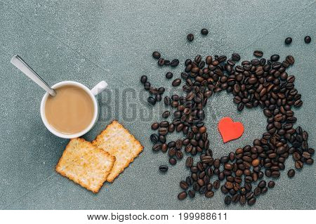 Breakfast for lovers. Coffee beans in the shape of a heart a Cup of coffee and biscuits on a grey backgroundtop view