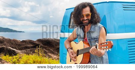 summer holidays, travel, music and people concept - young hippie man playing guitar at minivan car over island and sea background
