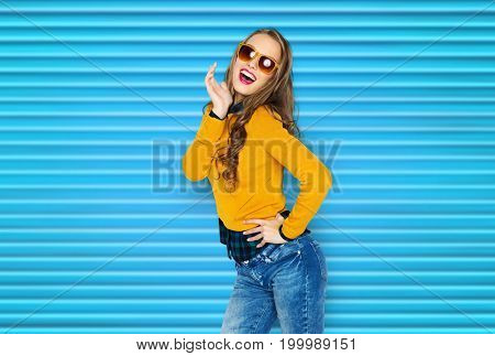 people, style and fashion concept - happy young woman or teen girl in casual clothes and sunglasses having fun over blue ribbed background