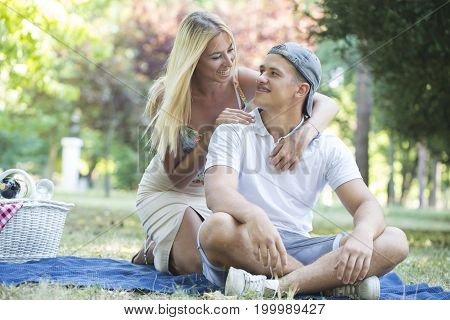 Happy Young Couple In Love Relaxing And Having Picnic In Park