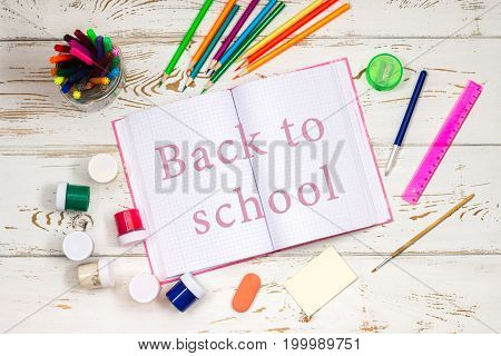 Outdoor Notebook Surrounded By School Supplies On A White Wooden Background With Empty Space For Ins