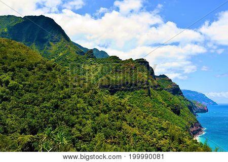 Lush tropical forest on mountainous terrain taken at the Napali Coast where mountains meet the sea taken in Kauai, HI