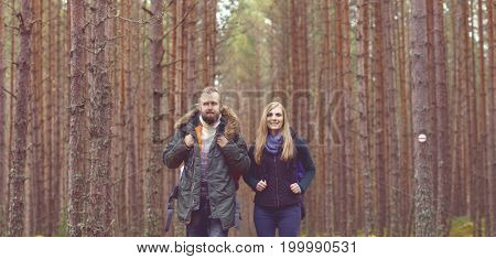 Young beautiful couple walking in forest. Camp, tourism, hiking concept.