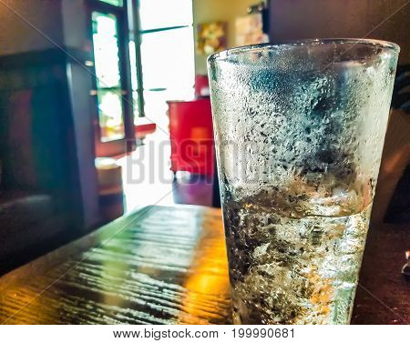 A table at a restaurant with a drinking glass full of ice with condensation in a blurred background.