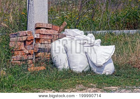 White bags with cement and sand near a pile of bricks in the grass