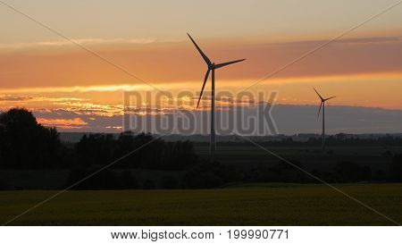 Wind turbines farms with rays of light at sunset in the background.