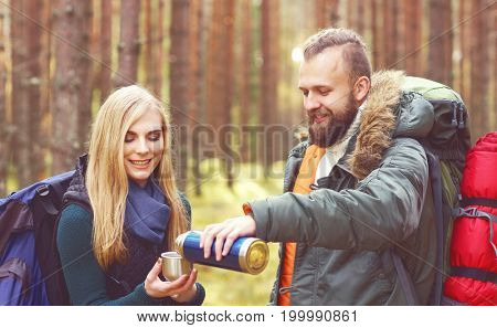 Young beautiful couple having a break in forest and drinking a tea. Camp, tourism, hiking concept.