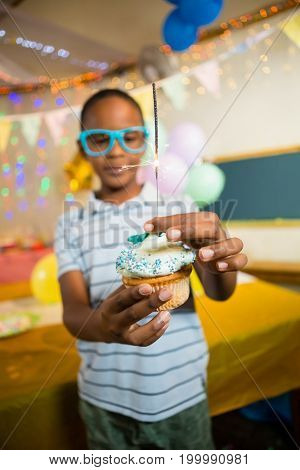 Cute boy decorating cupcake with sparkler during birthday party at home