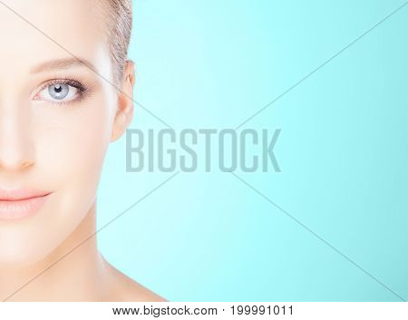 Beautiful female face over teal background