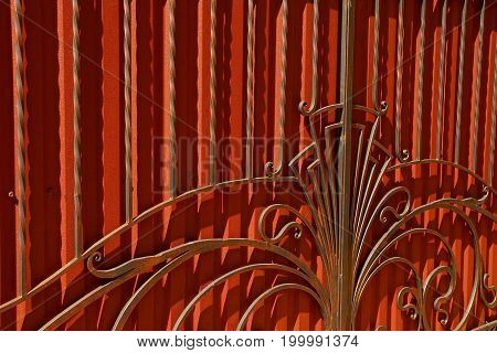 A fragment of red doors with forged bars and a beautiful pattern