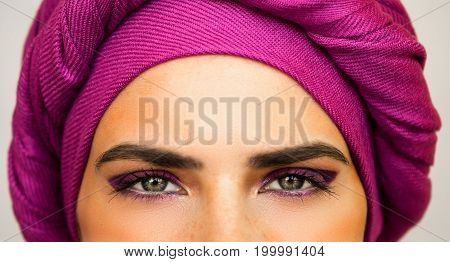 Beautiful European woman in a bright pink turban and beautiful makeup . The style of urban fashion. Portrait close up