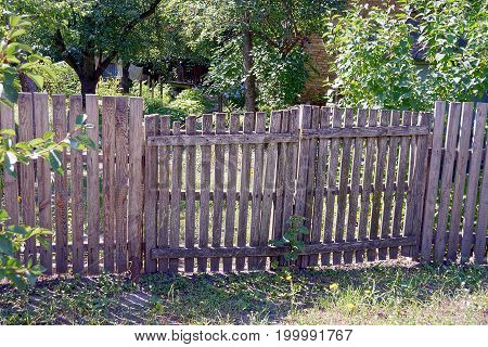 Gray fence with wicket gate in the grass