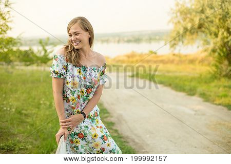 Half length portrait of charming positive woman dressed in long white summer dress happy smiling in sunset background. Beautiful woman enjoy.