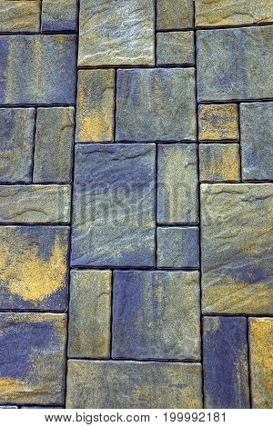 Stone background from a fragment of gray green colored paving tiles on the road