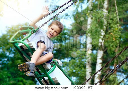 Happy boy riding in the park in the sunny afternoon