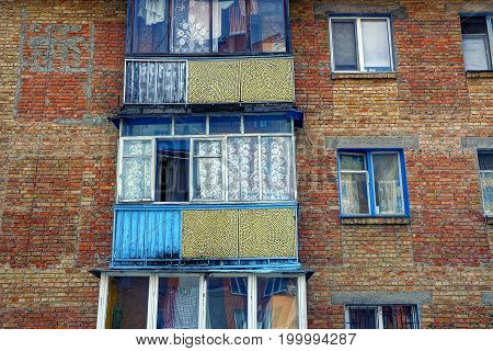 Old balconies with windows on the brick wall of the house