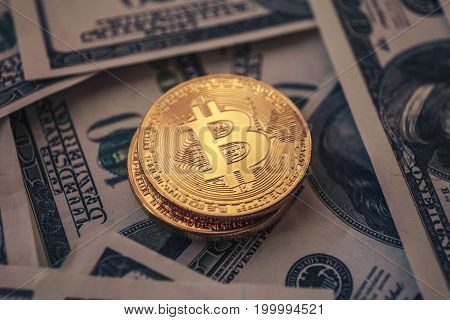 Several Bitcoin coins are stacked among dollars, selective focus, toned