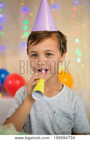 Boy blowing a party horn during birthday party at home