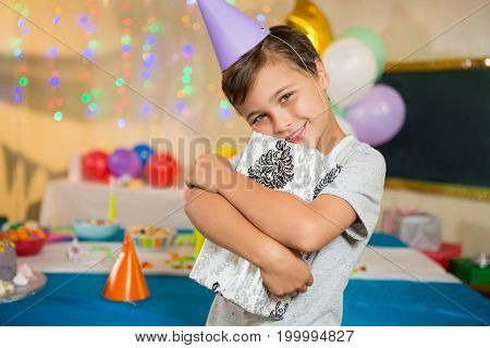 Portrait of boy embracing gift box during birthday party at home