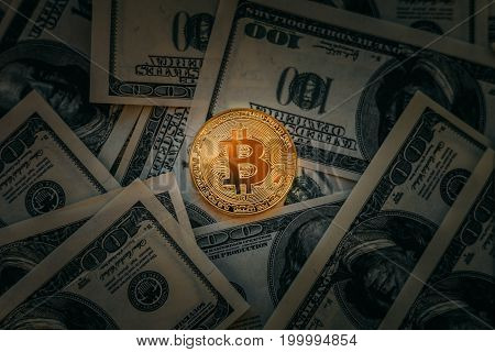 Bitcoin concept. Golden Bitcoin coin at dark background of cash money dollars, toned