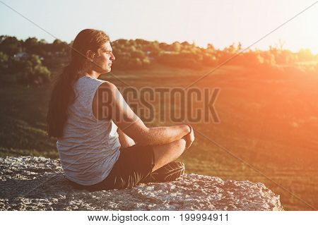 Young man with long hair sits at sunset on the edge of cliff or rock, toned