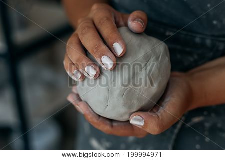 Potter is kneading clay, woman hands, working in pottery concept, selective focus