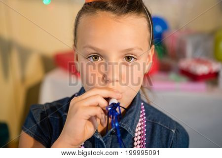 Girl blowing party horn during birthday party at home